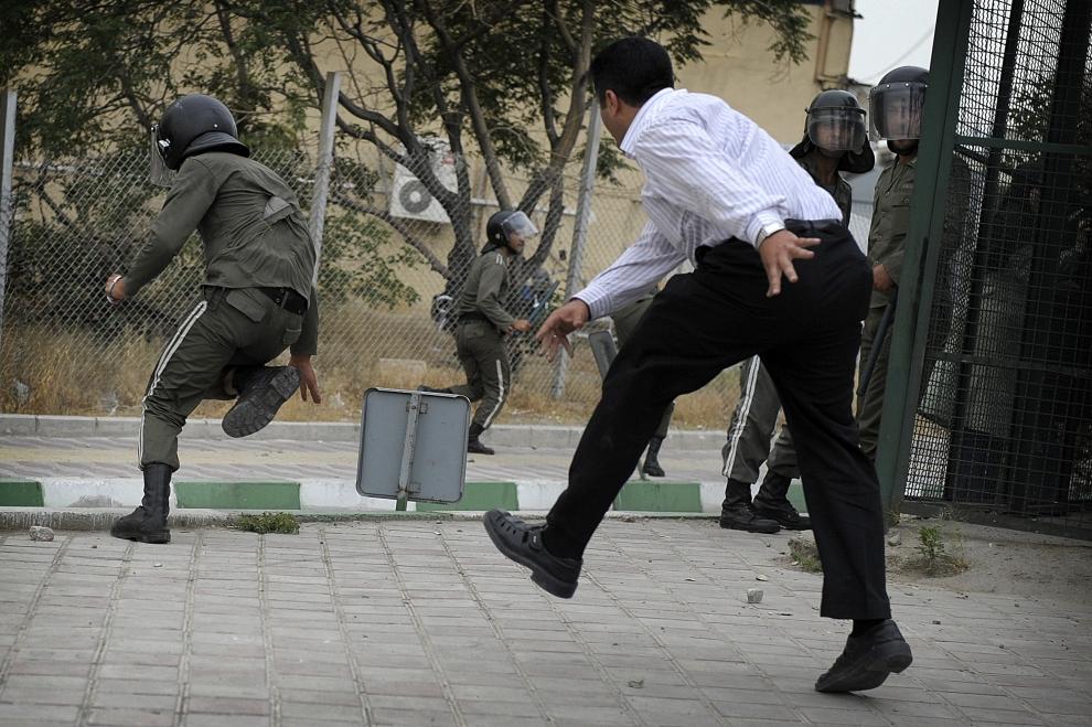 10. IRAN, Teheran, 13 czerwca 2009: Kamień rzucony przez protestującego dosięga policjanta. AFP PHOTO/OLIVIER LABAN-MATTEI