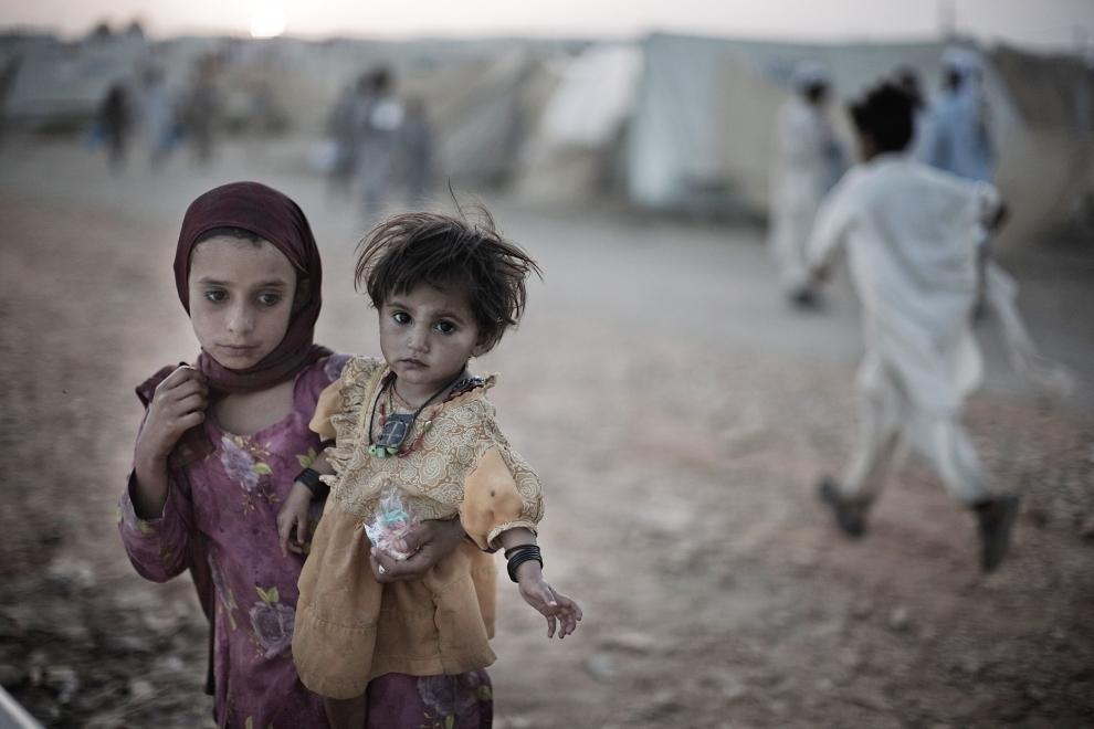 10. PAKISTAN, CHOTA LAHORE: Dziewczynki stoją wśród namiotów obozu dla uchodźców w Chota Lahore. (Foto: Daniel Berehulak/Getty Images)
