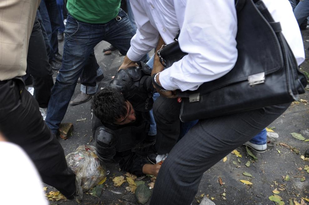 13. IRAN, Teheran, 13 czerwca 2009: Irański policjant z oddziałów tłumiących zamieszki upadł na ziemię wśród protestujących. AFP PHOTO/OLIVIER LABAN-MATTEI