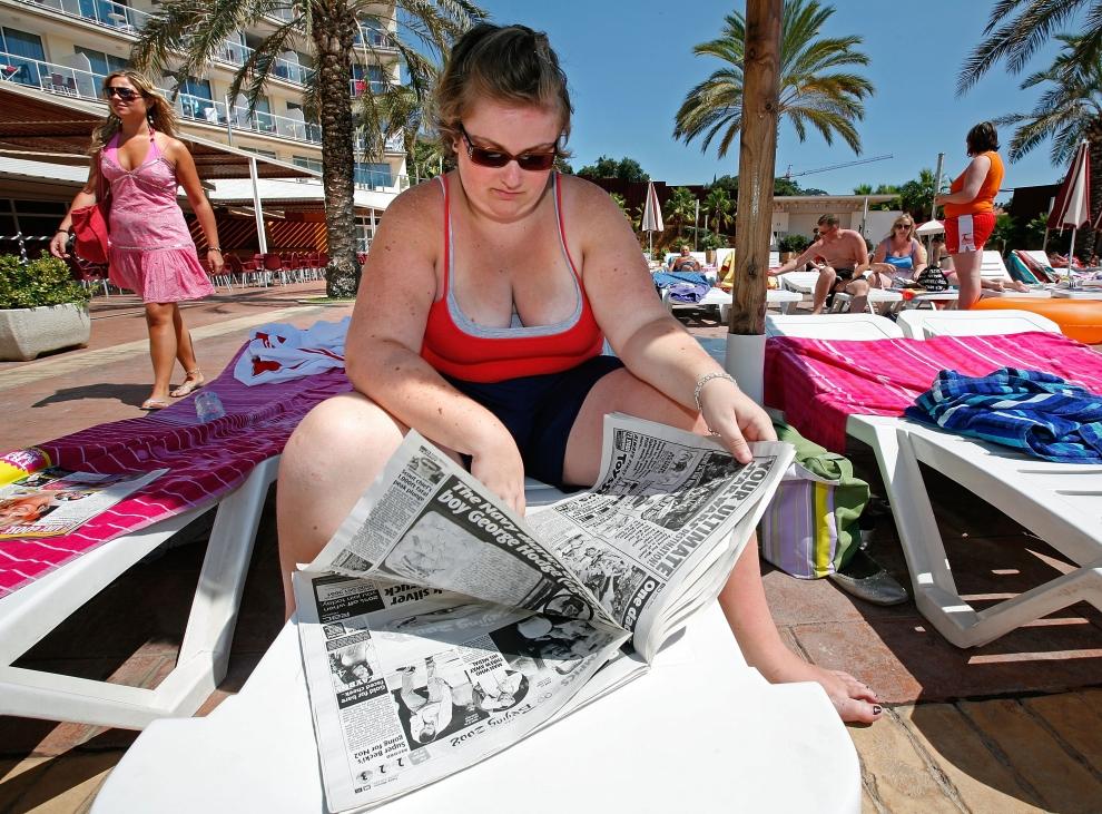 14. LLORET DE MAR, HISZPANIA - SIERPIEŃ: Shauna Quinn, studentka z Irlandii Północnej, czyta przywiezioną ze sobą gazetę. (Foto: Cate Gillon/Getty Images)