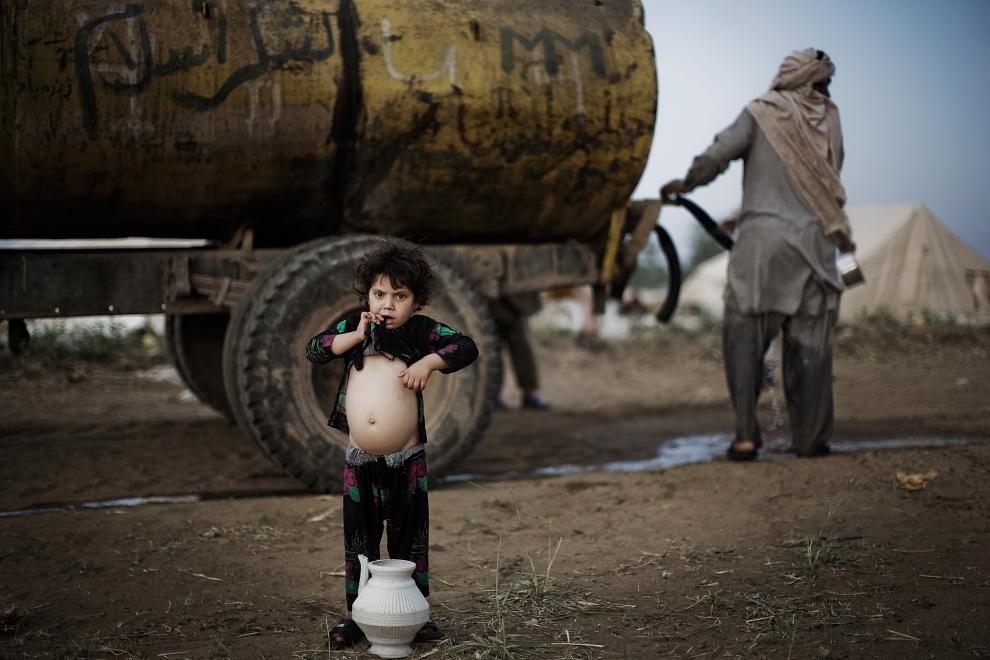 13. PAKISTAN, SWABI: Małe dziecko odpoczywa po naczerpaniu wody do naczynia. (Foto: Daniel Berehulak/Getty Images)