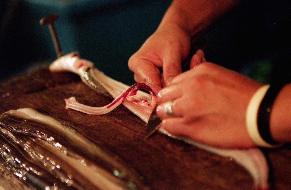 13. TOKIO - TARG RYBNY TSUKIJI: Sprzedawca ryb patroszy węgorza.  (Foto: Cameron Spencer/Getty Images)