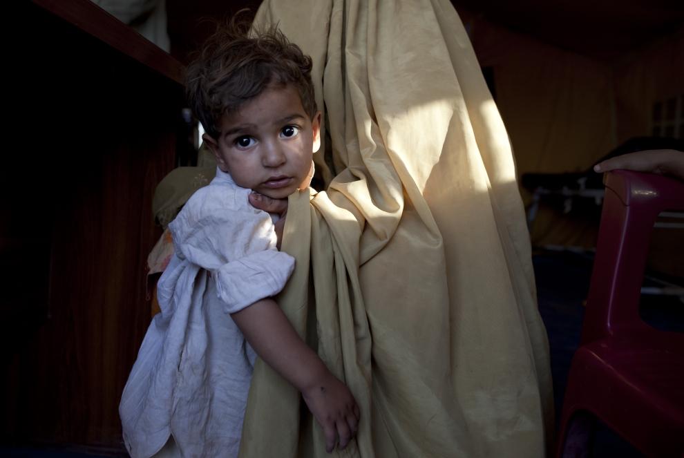 14. PAKISTAN, JALOZAI: Mała dziewczynka trzymana przez matkę czeka na zabieg medyczny. (Foto: Paula Bronstein /Getty Images)