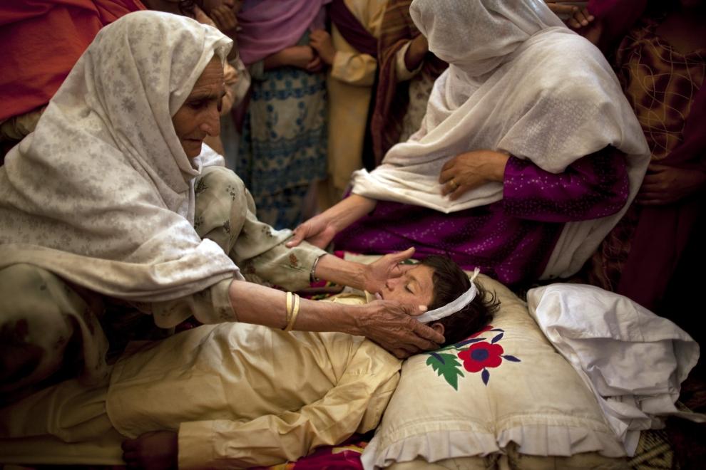 15. PAKISTAN, SWABI: Shamsum, dotyka twarzy swojego wnuka, który uległ wypadkowi podczas pływania w kanale obozu Chota Lahore. (Foto: Paula Bronstein/Getty   Images)