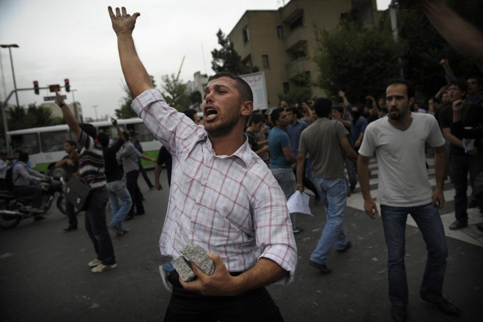 19. IRAN, Teheran, 13 czerwca 2009: Zwolennik Mir Hossein Mousawiego wyraża swoje niezadowolenie wykrzykując hasła. W rękach trzyma kamienie.  AFP PHOTO/OLIVIER LABAN-MATTEI