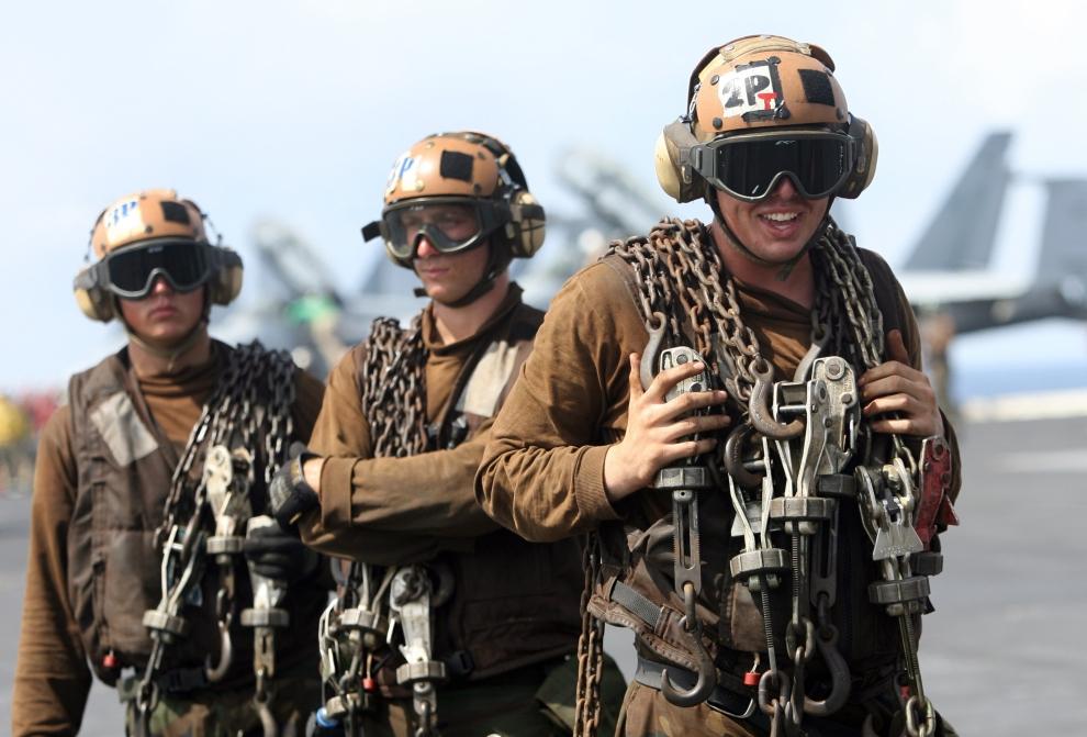 19. LOTNISKOWIEC USS KITTY HAWK: Członkowie załogi USS Kitty Hawk z łańcuchami do przeciągania sprzętu na pokładzie lotniskowca. AFP PHOTO/Deshakalyan CHOWDHURY