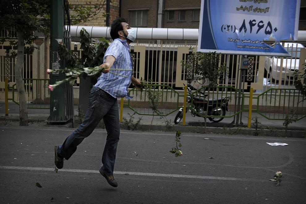 20. IRAN, Teheran, 13 czerwca 2009: Zwolennik Mir Hossein Mousawiego rzuca kwiatami podczas demonstracji przeciw   wynikom wyborów prezydenckich. AFP PHOTO/OLIVIER LABAN-MATTE