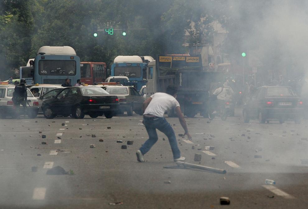 2. IRAN, Teheran, 13 czerwca 2009: Protestujący schyla się aby podnieść kamień. AFP PHOTO/BEHROUZ MEHRI