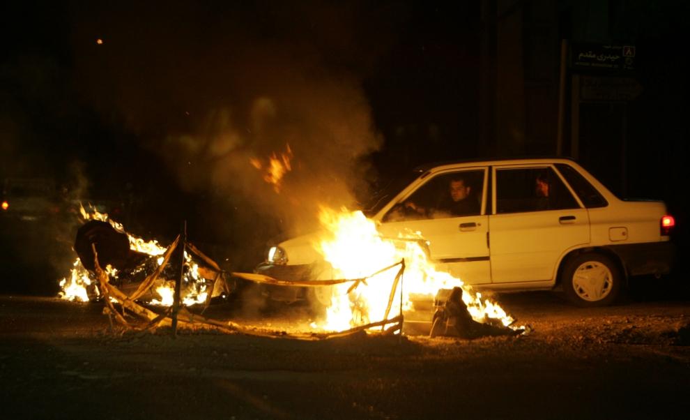 21. IRAN, Teheran, 13 czerwca 2009: Samochód wiozący zwolenników Mir Hossein Mousawiego mija płonący wrak.   AFP PHOTO/ATTA KENARE