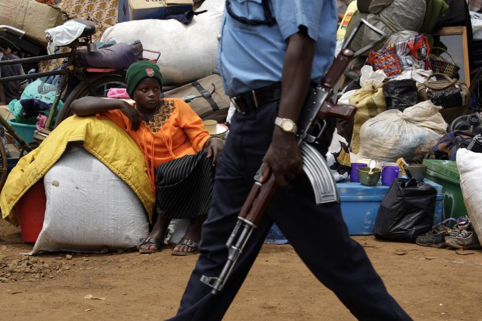 22. KENYA, TIGONI: Żołnierz z karabinem przechodzi obok kobiety siedzącej na ziemi w obozie dla uchodźców w Tigoni. (Foto: Paula Bronstein/Getty Images)