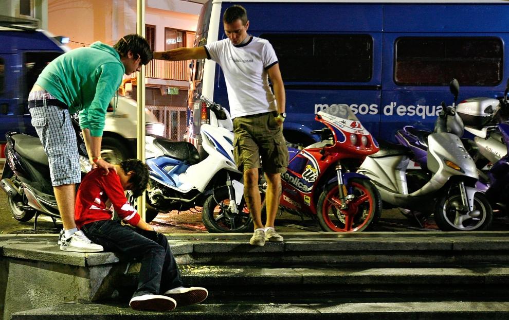 24. LLORET DE MAR, HISZPANIA - SIERPIEŃ: Przyjaciele pomagają turyście, który przesadził z alkoholem. (Foto: Cate Gillon/Getty Images)