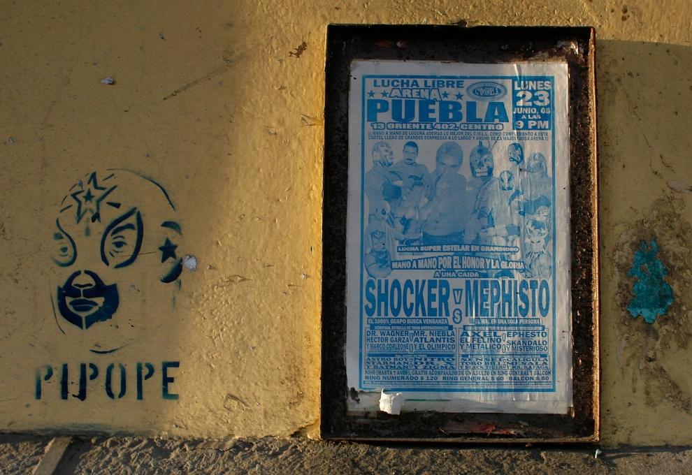 2. PUEBLO, MEKSYK: Graffiti przedstawiające gwiazdę lucha libre, Pipope, obok plakatu zapowiadającego walkę. (Foto: Paula Bronstein/Getty Images)