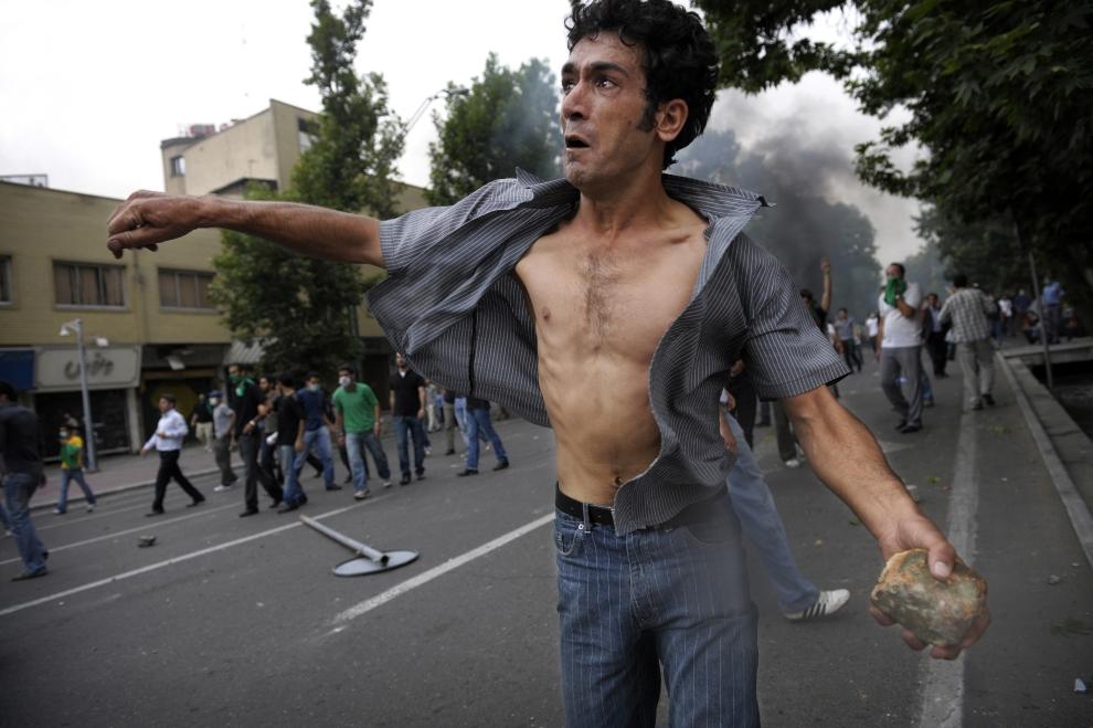 3. IRAN, Teheran, 13 czerwca 2009: Protestujący rzuca kamieniem w kierunku oddziałów policji. AFP PHOTO/OLIVIER LABAN-MATTEI