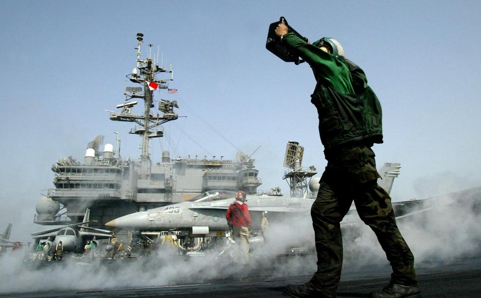 3. LOTNISKOWIEC USS KITTY HAWK: Transport myśliwca szturmowego F/A-18C Hornet na pas startowy lotniskowca. AFP PHOTO/Leila GORCHEV