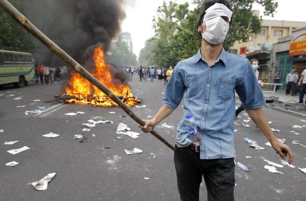 5. IRAN, Teheran, 13 czerwca 2009 : Zwolennik pokonanego w wyborach prezydenckich Mir Hossein Mousawiego. W tle płonący motocykl.  AFP PHOTO/BEHROUZ MEHRI