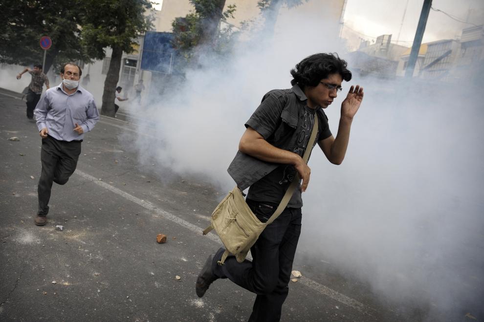 6. IRAN, Teheran, 13 czerwca 2009: Protestujący uciekają przed rozpylonym przez policję gazem łzawiącym. AFP PHOTO/OLIVIER LABAN-MATTEI