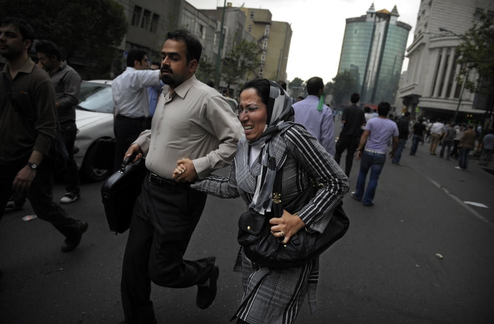 7. IRAN, Teheran, 13 czerwca 2009: Przypadkowi przechodnie uciekają z ogarniętej zamieszkami ulicy.  AFP PHOTO/OLIVIER LABAN-MATTEI
