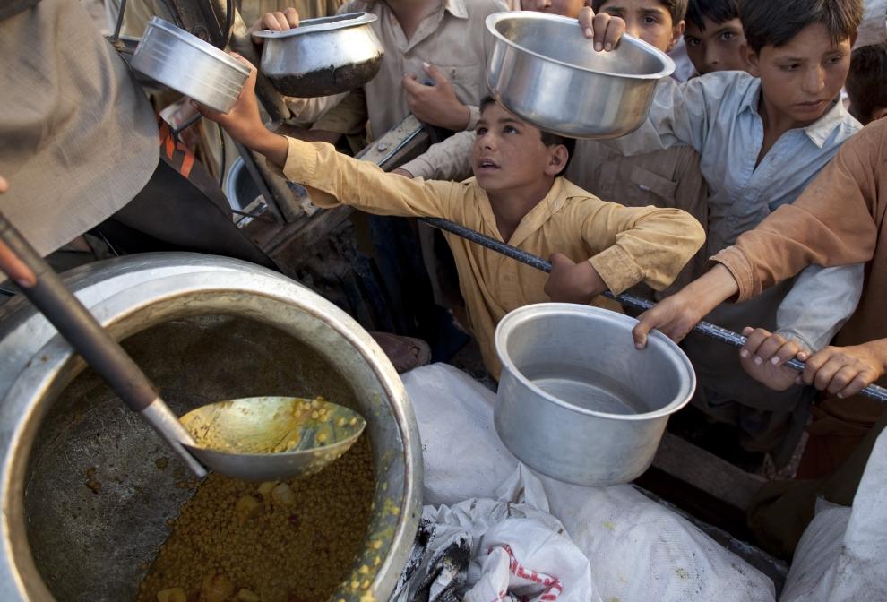 7. PAKISTAN, JALOZAI: Chłopiec stara się podać swoją miskę rozlewającym zupę z naczepy samochodu. (Foto: Paula Bronstein /Getty Images)