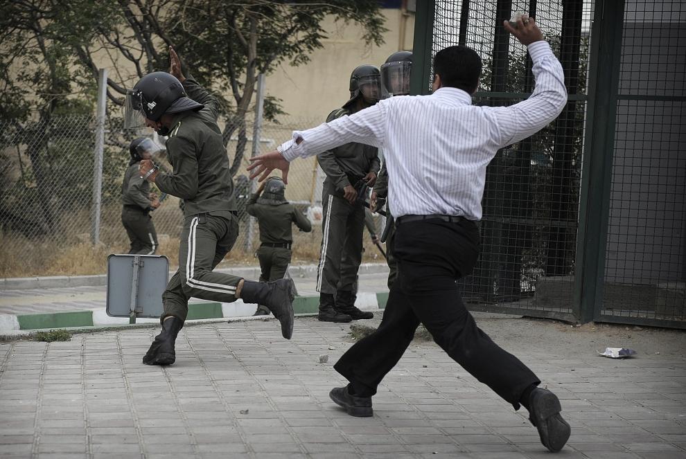 9. IRAN, Teheran, 13 czerwca 2009: Protestujący ciska kamień w kierunku policjanta z oddziałów tłumiących zamieszki. AFP PHOTO/OLIVIER LABAN-MATTEI