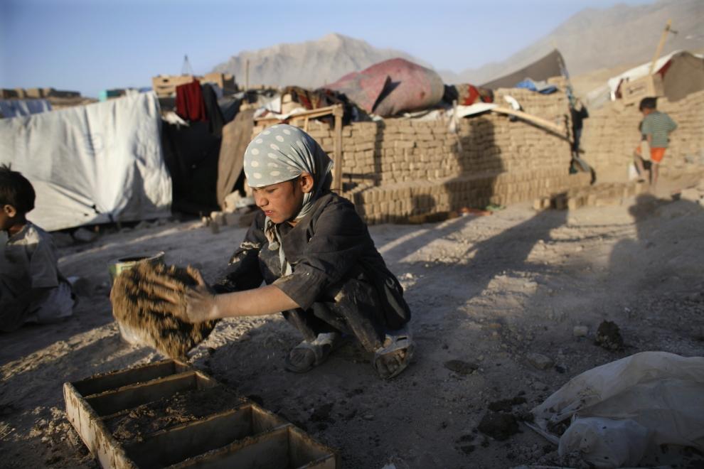 10. AFGANISTAN; Barikab: Trzynastoletni Firoza formuje cegły z gliny, z których wybudowany zostanie jego nowy dom. (Foto: Paula Bronstein/Getty Images)
