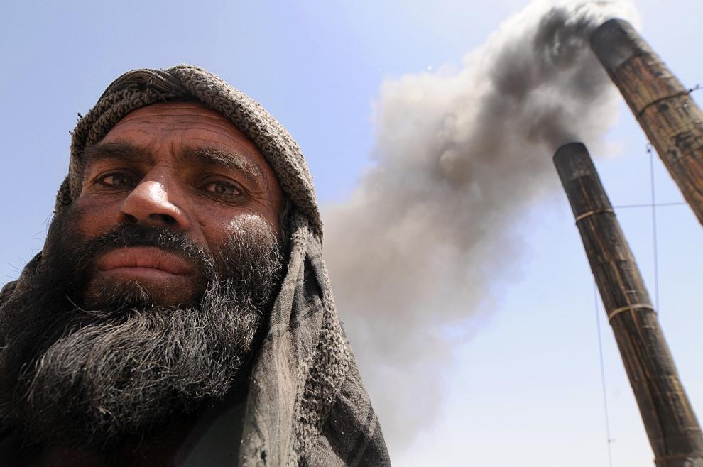 14. AFGANISTAN, Kabul: Pracownik fabryki na tle kominów pieców do wypalania cegieł. AFP PHOTO/SHAH Marai