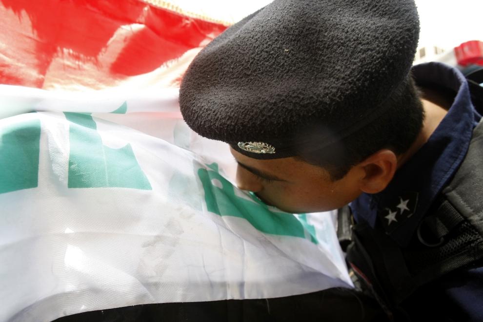 18. IRAK, Bagdad: Policjant całuje flagę narodową swojego kraju. AFP PHOTO / SABAH ARAR
