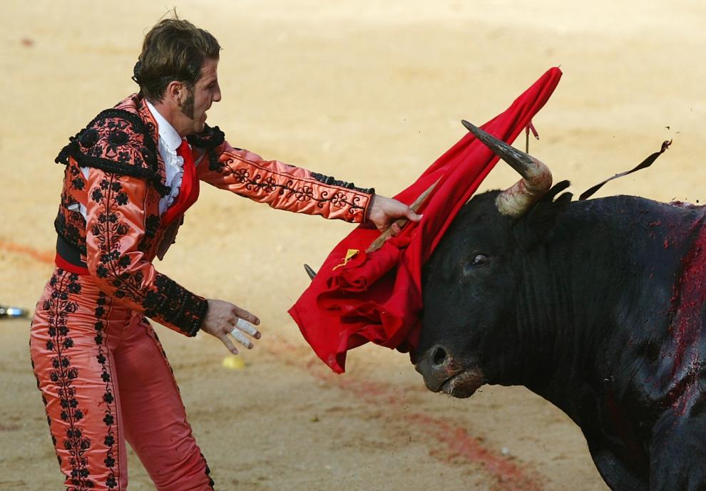 22. HISZPANIA, Pampeluna: Matador Juan Jose Padilla stara się zatrzymać byka. AFP PHOTO / RAFA RIVAS