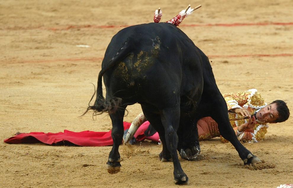 "23. HISZPANIA, Pampeluna: Matador Jose P. Prados ""El Fundi"" próbujący uniknąć szarży byka. AFP PHOTO / RAFA RIVAS"