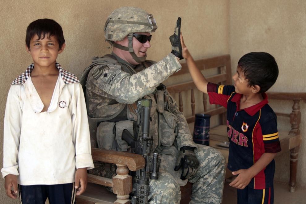 28. IRAK, Khan Bani Saad: Dziecko bawi się z żołnierzem podczas wizyty Amerykanów w domu starszyzny miejscowości Khan Bani Saad. AFP PHOTO / AHMAD AL-RUBAYE