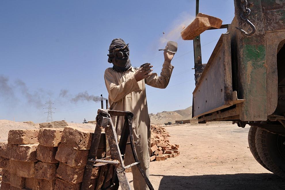 4. AFGANISTAN, Kabul: Pracwonik fabryki ładuje cegły na ciężarówkę. AFP PHOTO/SHAH Marai