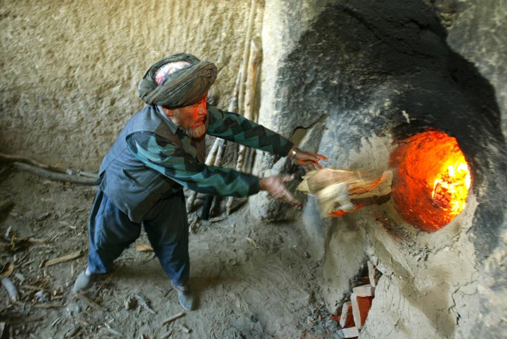 7. AFGANISTAN, Kabul: Pracownik dokłada drewno do pieca służacego do wypalania cegieł. (Foto: Paula Bronstein/Getty Images)