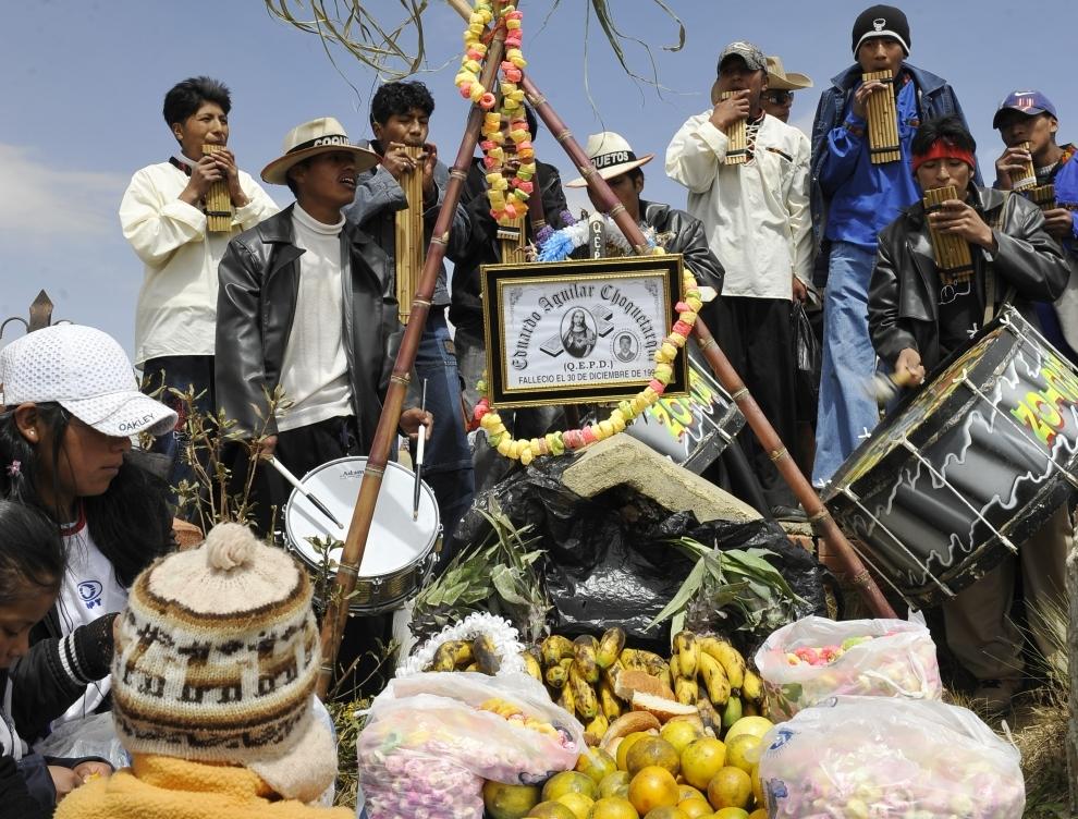 12. BOLIWIA, El Alto: Rodzina zmarłego, w towarzystwie muzyków, składa ofiary z jedzenia na grobie bliskiej osoby. AFP/PHOTO/AIZAR RALDES