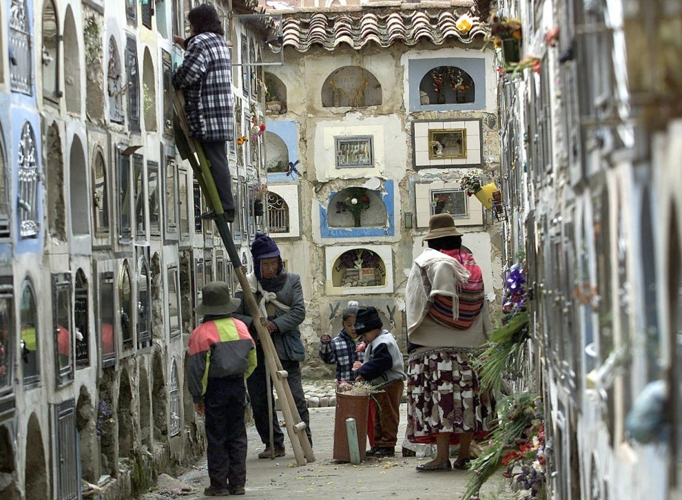18. BOLIWIA, La Paz: Rodzina porządkuje miejsce spoczynku zmarłego. AFP PHOTO/AIZAR RALDES
