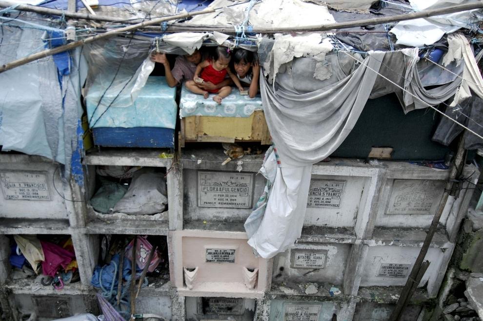20. FILIPINY, Navotas: Część opuszczonych grobów zamieszkiwana jest przez ludzi, których nie stać nawet na wynajmowanie lokum. W dniu Wszystkich Świętych   wmieszani są w tłum odwiedzających groby bliskich. AFP PHOTO/NOEL CELIS