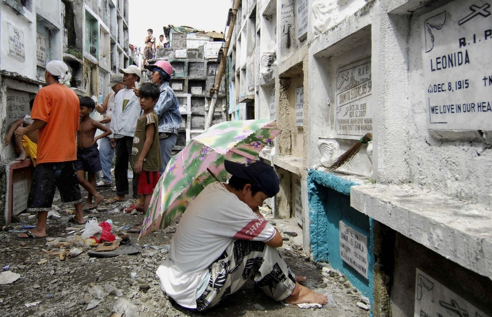 21. FILIPINY, Navotas: Kobieta modląca się przy grobie krewnego. AFP PHOTO/NOEL CELIS