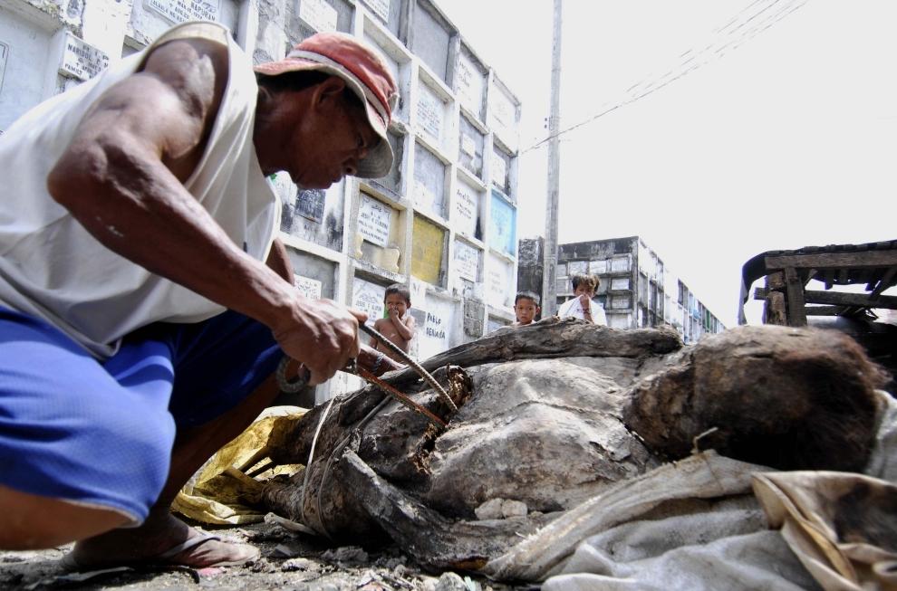 """24. FILIPINY, Navotas: Dozorca cmentarza tnie zmumifikowane zwłoki, aby przenieść je do mniejszego grobu, w przeddzień """"Zaduszek"""". AFP PHOTO/NOEL CELIS"""