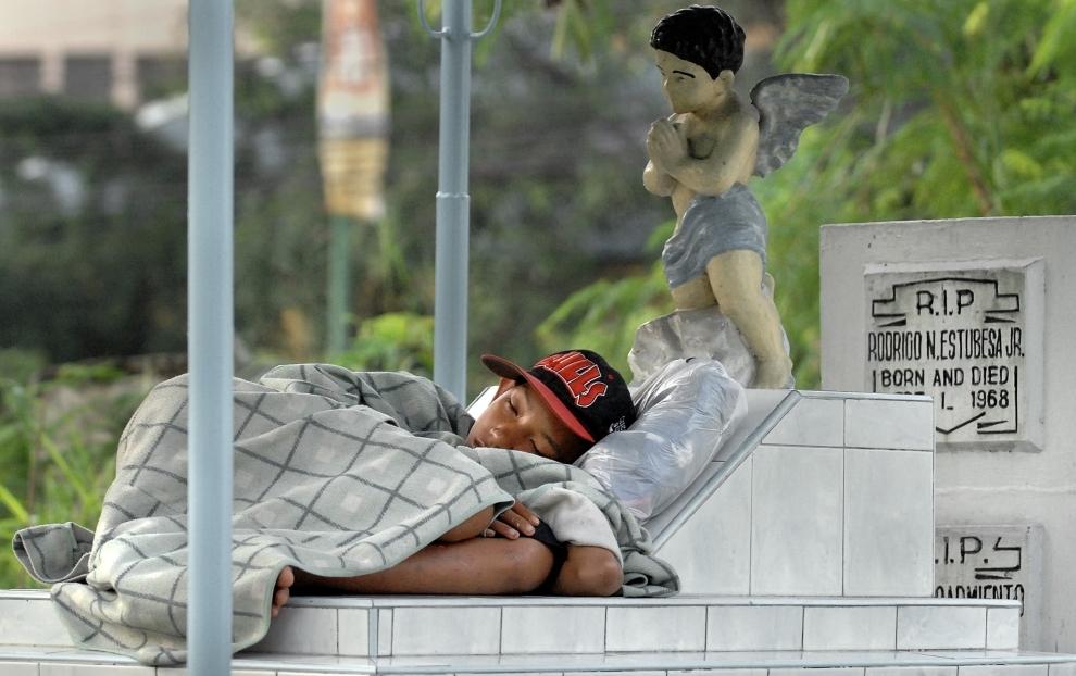 25. FILIPINY, Manila: Chłopiec śpiący na grobie w dniu Wszystkich Świętych. W ciągu lat zwyczaje związane z tym dniem ewoluowały w coś na kształt fiesty. AFP   PHOTO/Jay DIRECTO