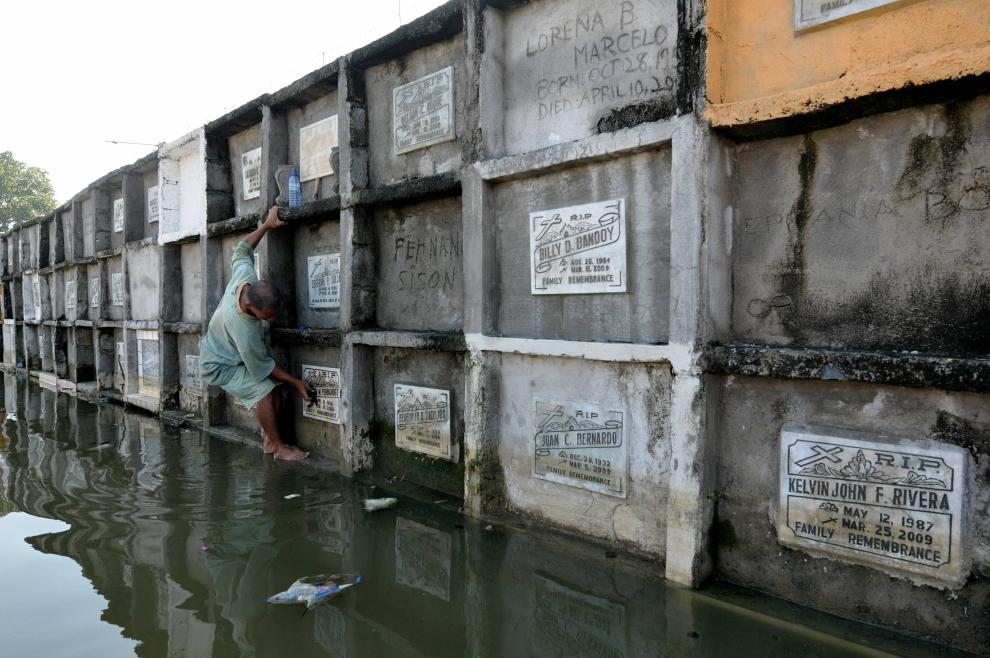 27. FILIPINY, Manila: Raffy Fernandez porządkujący grób zmarłej matki na zalanym cmentarzu w Angono. AFP PHOTO/JAY DIRECTO