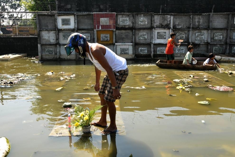 28. FILIPINY, Manila: Joel Lebrilla składa kwiaty i zapala świece na grobie, w którym jak sądzi, pochowana jest jego matka. Identyfikację miejsca pochówku utrudnia wezbrana woda. AFP PHOTO/JAY DIRECTO