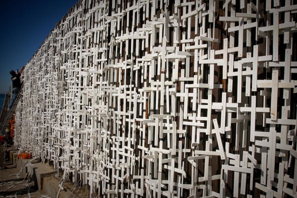 """6. MEKSYK, Tijuana: Członkowie organizacji """"Pro Defensa del Migrante"""" umieścili 30 października na murze granicznym między USA i Meksykiem 5 tys. krzyży.   Upamiętniają one liczbę osób, które od 1995 roku zginęły przedostając się do USA. AFP PHOTO / Daniel CONEJO"""