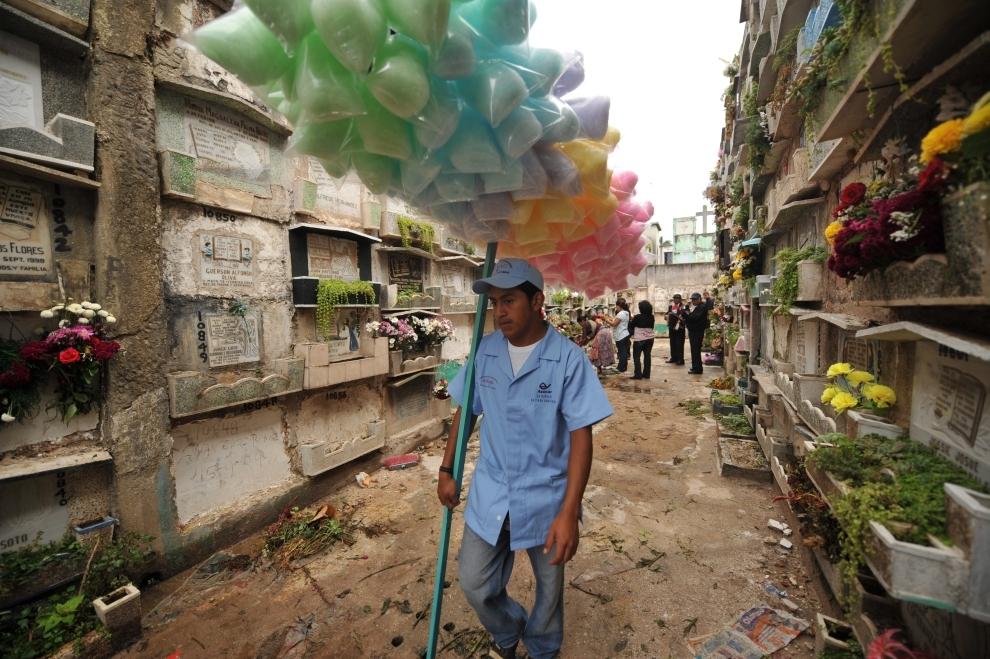 9. GWATEMALA, Gwatemala: Sprzedawca waty cukrowej przechodzi alejką między grobami. AFP PHOTO Johan ORDONEZ.