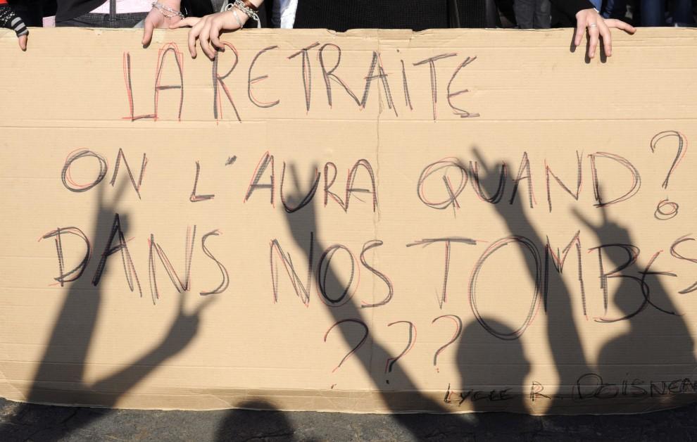 """16. FRANCJA, Paryż, 14 października 2010: Protestujący studenci trzymają karton z hasłem: """"Kiedy przejdziemy na emeryturę? W grobach?"""". AFP PHOTO BORIS HORVAT"""