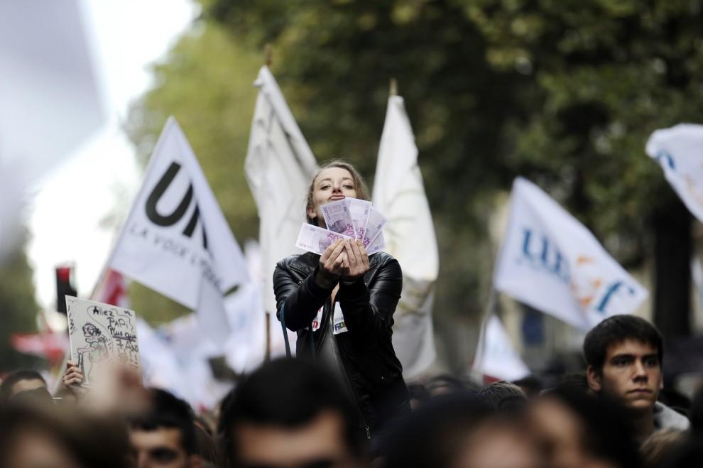 20. FRANCJA, Paryż, 16 października 2010: Studentka z plikiem fałszywych banknotów z podobiznami polityków. AFP PHOTO FRED DUFOUR
