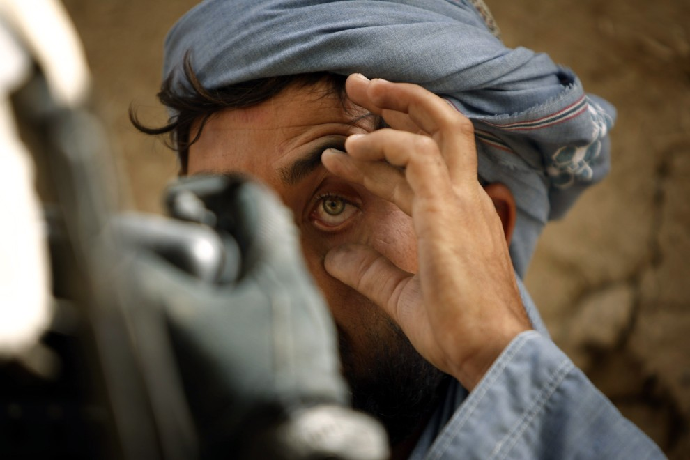 19. AFGANISTAN, Jellawar, 5 października 2010: Żołnierz wykonuje zdjęcie tęczówki zatrzymanego mężczyzny. AFP PHOTO/PATRICK BAZ