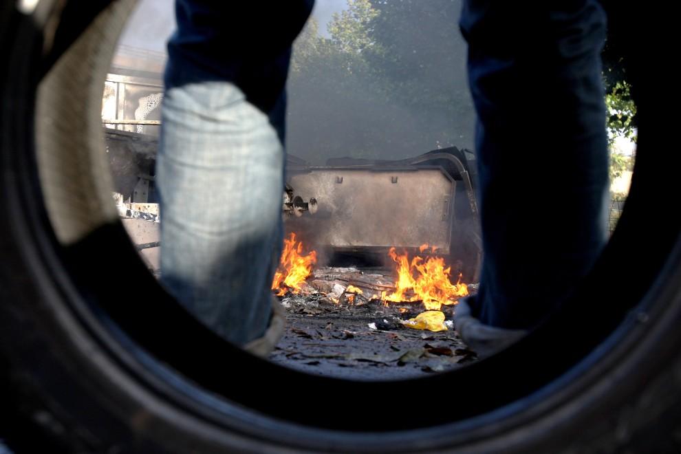 1. FRANCJA, Caen, 19 października 2010: Protestujący opiera się o oponę i przygląda płonącemu samochodowi.  AFP PHOTO KENZO TRIBOUILLARD