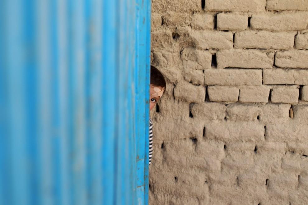20. AFGANISTAN, Fajzabad, 2 października 2010: Chłopiec wychyla się zza drzwi małego sklepu. (Foto: Miguel Villagran/Getty Images)