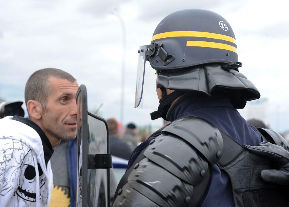 23. FRANCJA, Ambes, 19 października 2010: Jeden z demonstrujących rozmawia z policjantami. AFP PHOTO JEAN PIERRE MULLER