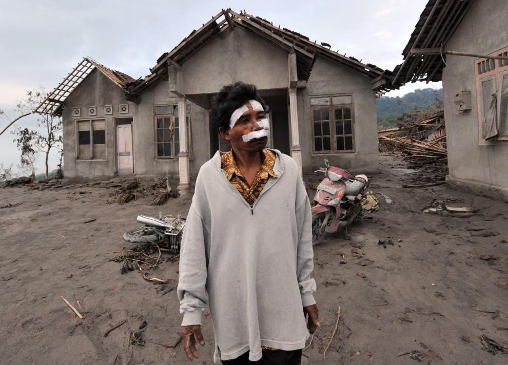 23. INDONEZJA, Kinahrejo, 28 października 2010: Mukiji, którego brat nie przeżył erupcji wulkanu, patrzy na pozostałości po domu krewnych. AFP PHOTO / ADEK BERRY