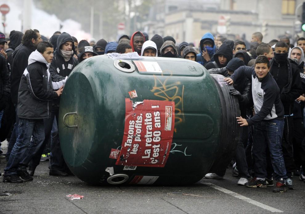 26. FRANCJA, Lyon, 19 października 2010: Licealiści toczą ulicą pojemnik na odpady. AFP PHOTO/PHILIPPE DESMAZES