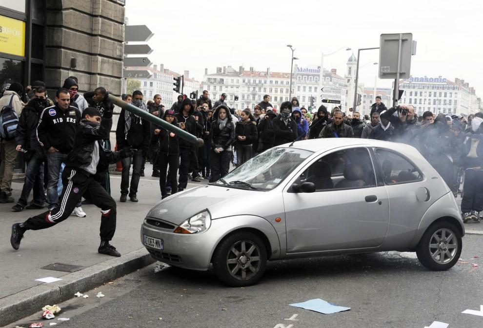 28. FRANCJA, Lyon, 19 października 2010: Chłopak demoluje samochód podczas demonstracji w Lyonie. AFP PHOTO/PHILIPPE DESMAZES